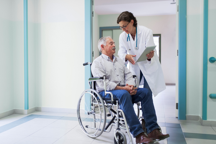 Case manager reviewing documents with patient in wheel chair