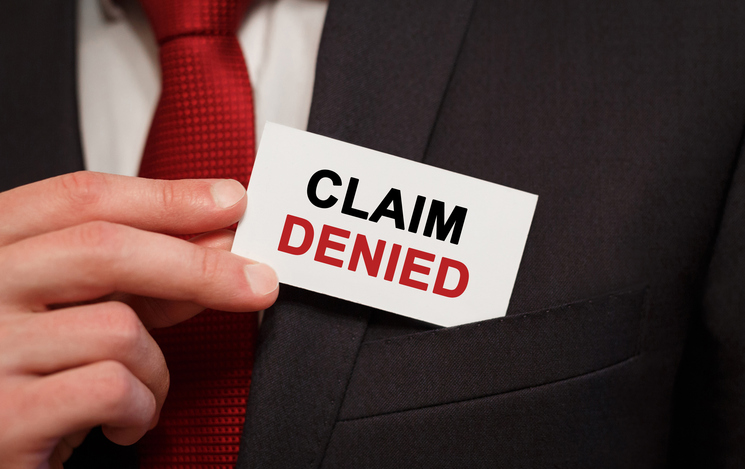 Businessman holding claim denials card